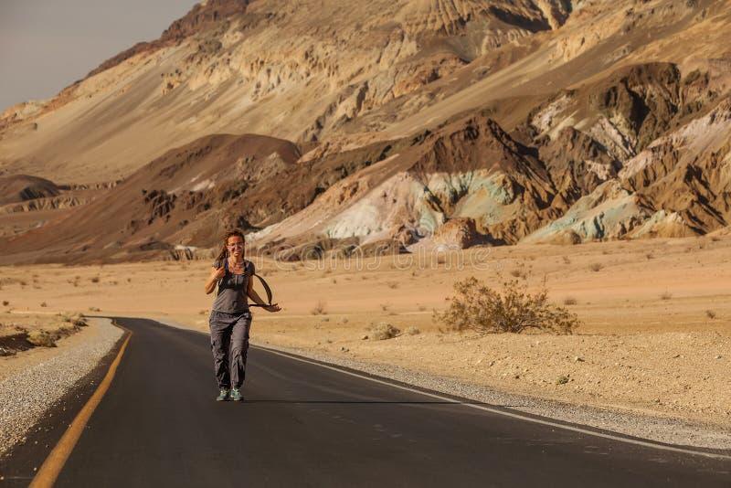 Liftervrouw die op een weg in de V.S. lopen stock afbeelding