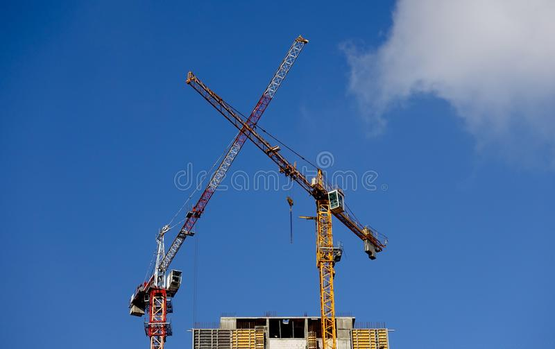 Lifting cranes tower above the house. Lifting tower cranes on the construction of a house. Low angle. Blue sky above the building. sunny day stock photography