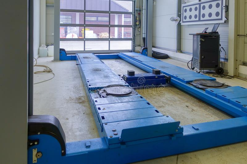 A lifting platform in a car repair shop. A blue lifting platform for cars in a workshop stock photos