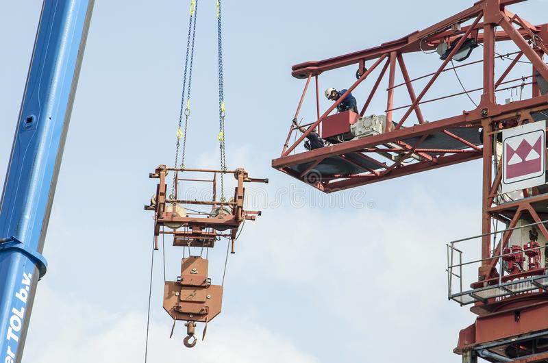 Lifting section of tower crane. Rotterdam, The Netherlands, August 28, 2018: two construction workers working on the attachment of the lifting mechanism to the royalty free stock photo