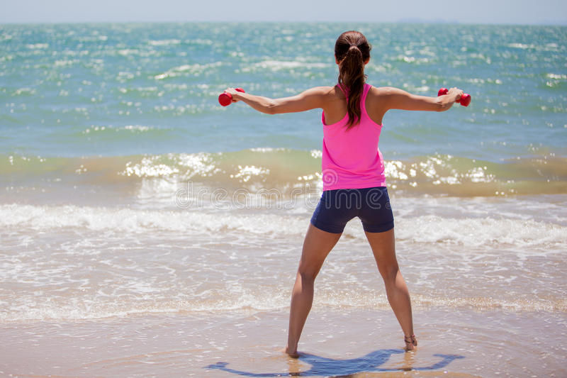 Lifting some weights at the beach. Athletic young woman lifting a couple of dumbbells at the beach stock photos