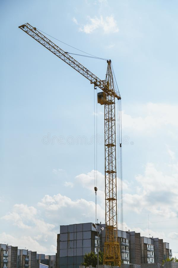 Lifting tower crane against cloudy sky background. Lifting tower crane on the construction of a multi-storey house against a cloudy sky background view from stock image