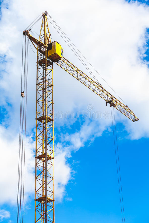 Lifting tower crane on background the cloudy sky. Yellow hoisting tower crane on a background of cloudy sky view from below royalty free stock photos