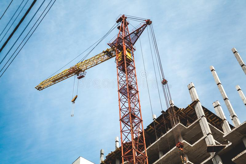 Lifting tower crane on frame of frame building. Yellow lifting tower crane on the construction of a multi-storey house against the background of a cloudy sky royalty free stock photo