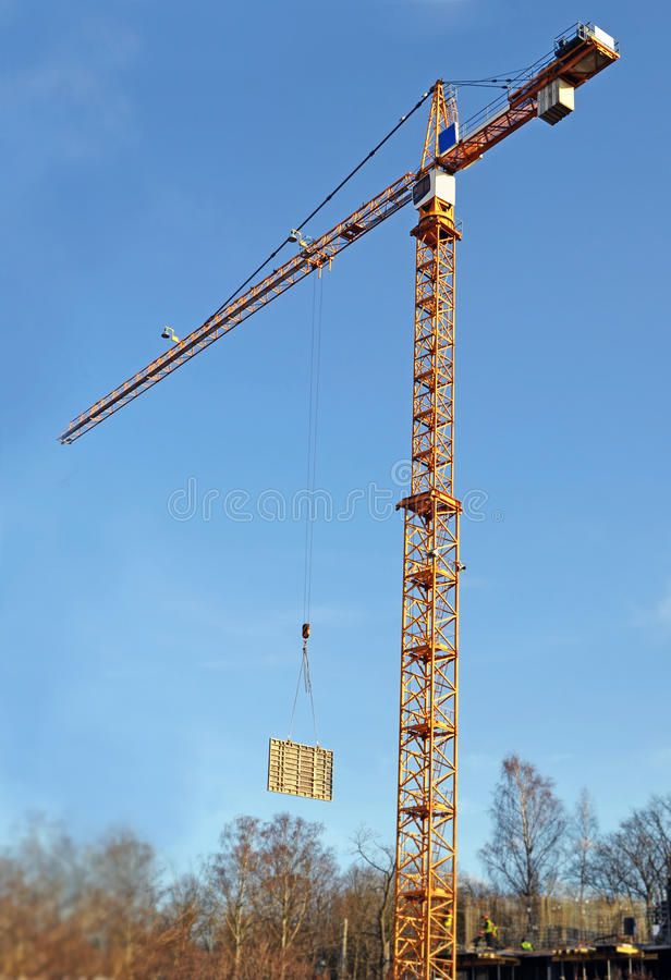 Lifting the tower crane moves freight. Construction block on blur building site against blue sky royalty free stock photos
