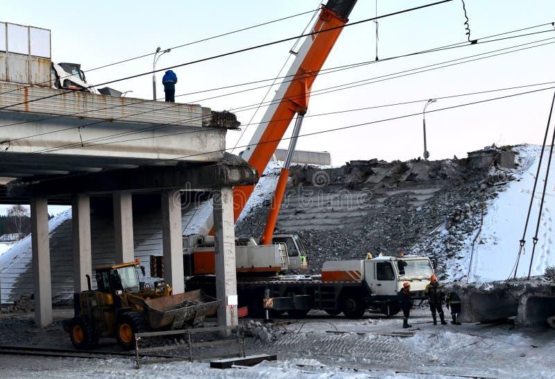Lifting truck crane, dismantling a large reinforced concrete slab,. Construction of an automobile bridge at a construction site royalty free stock photos