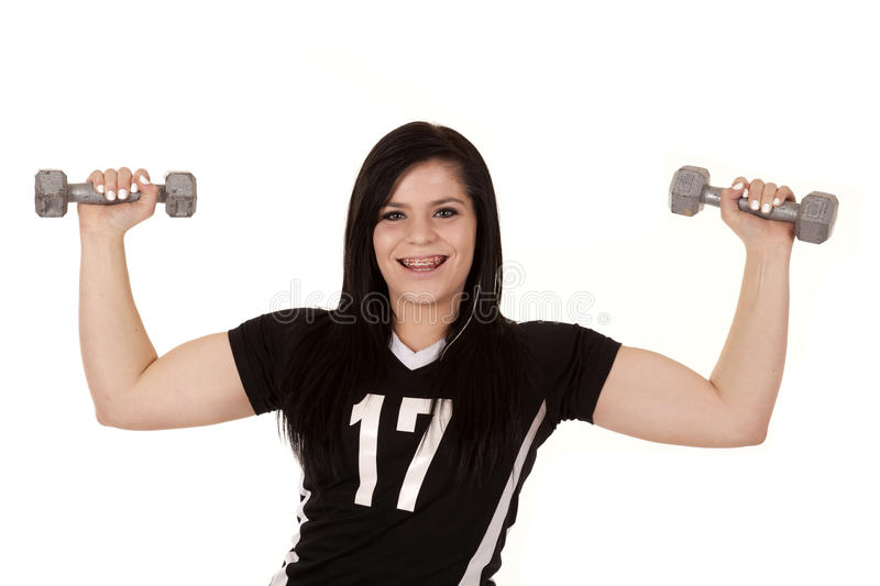 Lifting weights. A teen girl lifting weights and showing off her muscles stock photo