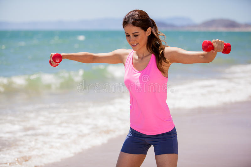 Lifting weights on a sunny day. Young woman practicing a dumbbell routine at the beach on a sunny day stock images