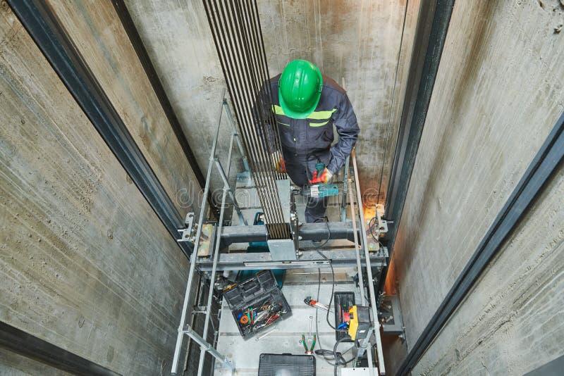 Liftmachinist die lift in liftschacht herstellen stock afbeelding