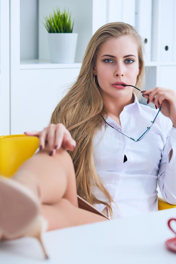 Ligón de la oficina - mujer atractiva que liga sobre el escritorio con su compañero de trabajo o jefe fotografía de archivo