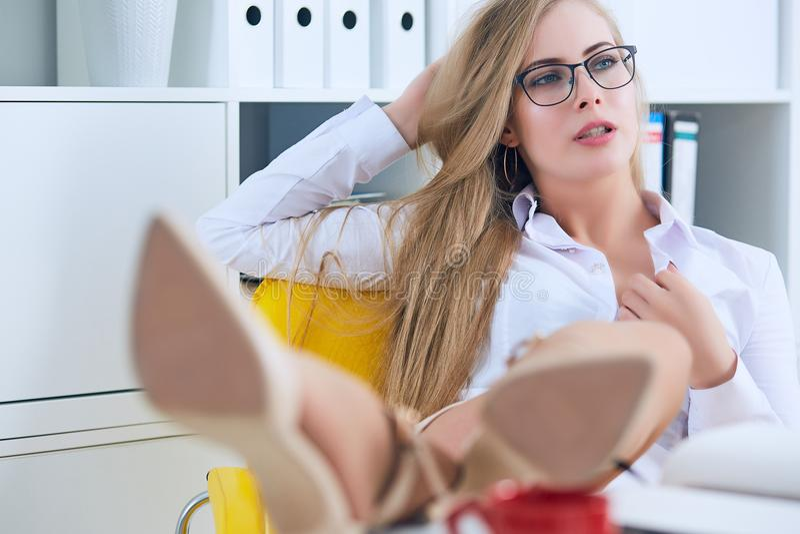 Ligón de la oficina - mujer atractiva que liga sobre el escritorio con su compañero de trabajo o jefe imagen de archivo libre de regalías