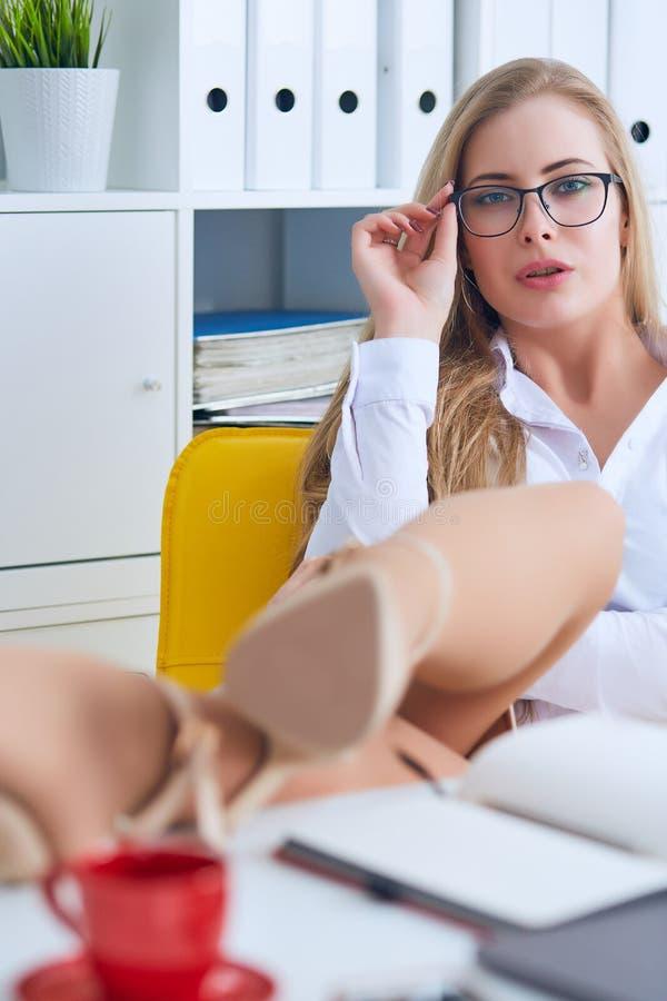 Ligón de la oficina - mujer atractiva que liga sobre el escritorio con su compañero de trabajo o jefe foto de archivo