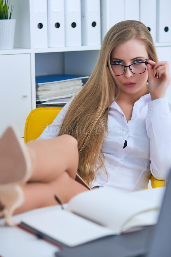 Ligón de la oficina - mujer atractiva que liga sobre el escritorio con su compañero de trabajo o jefe imagen de archivo