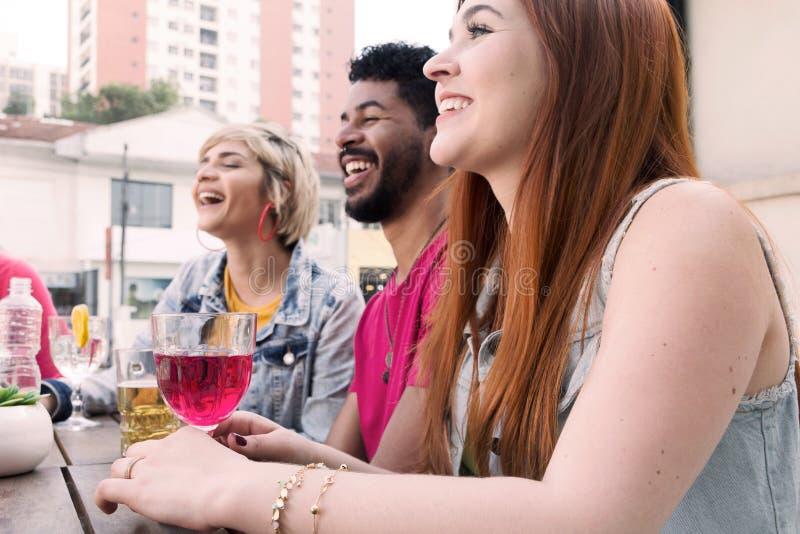 Ligação do grupo de raça misturada e beber na barra do café exterior Sprin imagem de stock royalty free