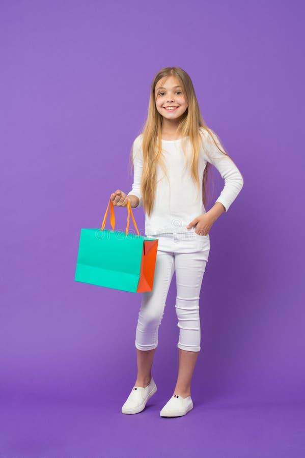 Ligação em ponte e calças brancas vestindo da menina isoladas no fundo roxo Criança com a cara alegre que guarda o saco de papel  imagem de stock royalty free