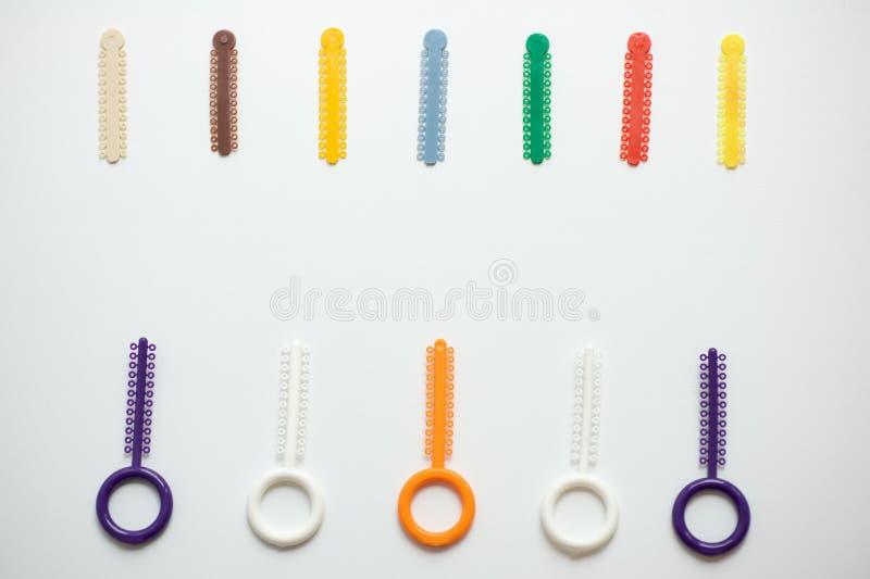 Ligaduras ortodônticas multi-coloridas para o alinhamento dos dentes do orthodontist em um fundo claro foto de stock royalty free
