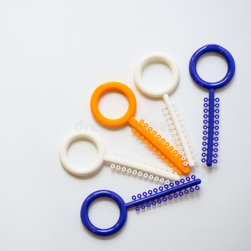 Ligaduras ortodônticas multi-coloridas para o alinhamento dos dentes do orthodontist em um fundo claro fotografia de stock royalty free