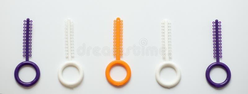 Ligaduras ortodônticas multi-coloridas para o alinhamento dos dentes do orthodontist em um fundo claro fotos de stock