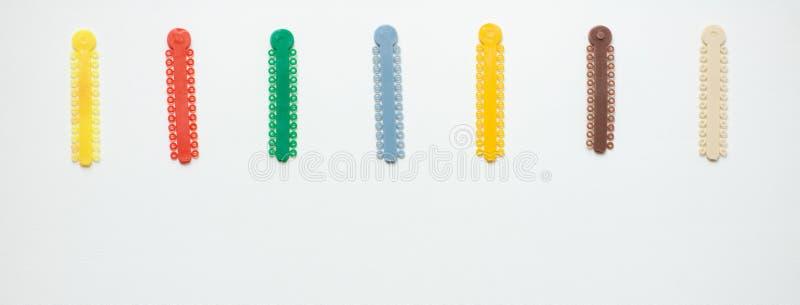 Ligaduras ortodônticas multi-coloridas para o alinhamento dos dentes do orthodontist em um fundo claro imagens de stock royalty free