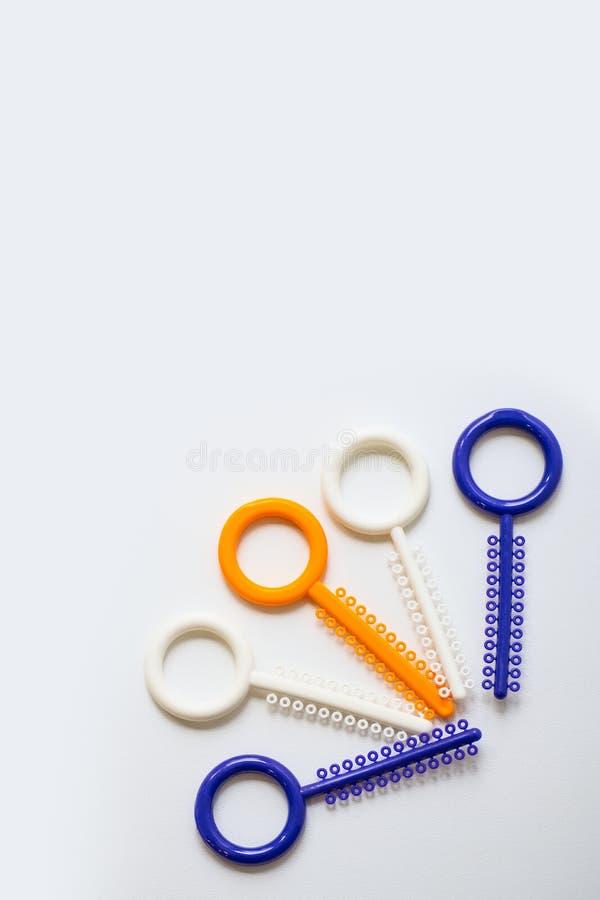 Ligaduras ortodônticas multi-coloridas para o alinhamento dos dentes do orthodontist em um fundo claro fotos de stock royalty free
