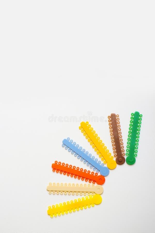 Ligaduras ortodônticas multi-coloridas para o alinhamento dos dentes do orthodontist em um fundo claro imagem de stock royalty free