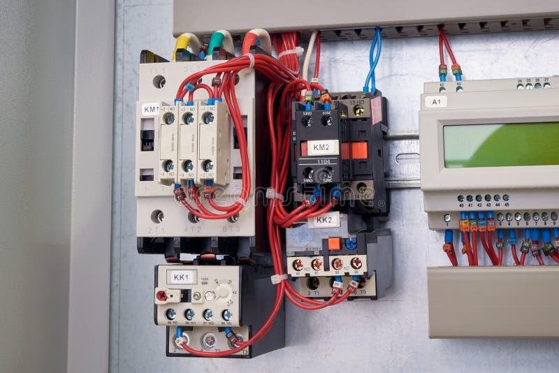 Ligando o conjunto dos contatores e de relés térmicos no armário elétrico fotos de stock royalty free