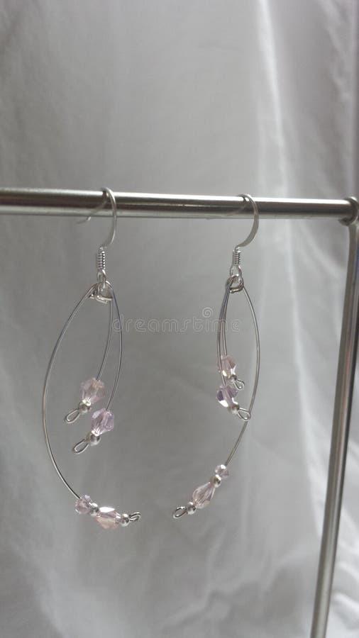 Ligeros curvada palidecen - plata rosada de los pendientes del estilo del descenso del cristal y de la perla plateada fotografía de archivo libre de regalías