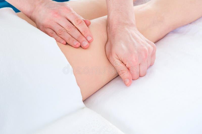 Ligga för kvinna som är framåt medan en terapeut som inomhus masserar hennes höft arkivfoton
