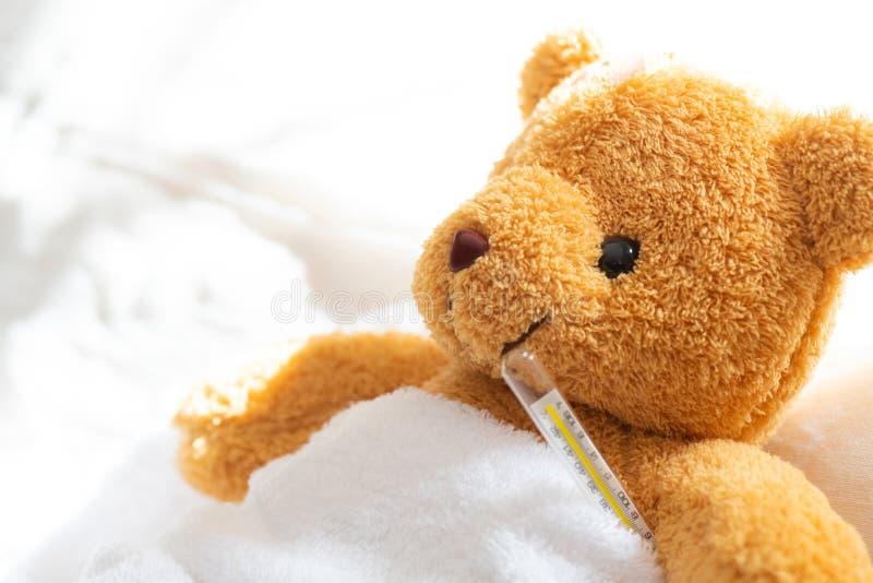 Ligga för nallebjörn som är sjukt i sjukhussäng med med termometern royaltyfri foto