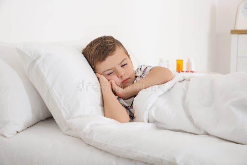 ligga för underlagpojke som är sjukt Liten tålmodig väntande på doktor royaltyfri bild