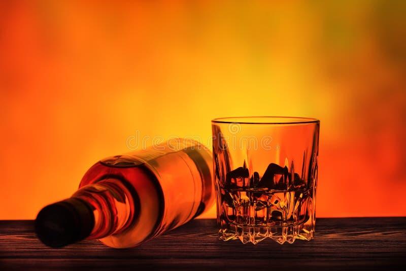 Liggande flaska och ett exponeringsglas av whisky med is arkivbild