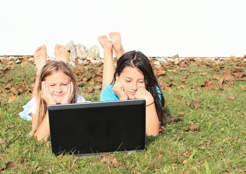Liggande flickor som håller ögonen på anteckningsboken arkivbilder