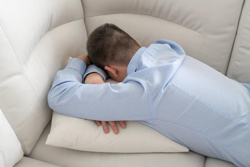 Liggande framsida för deprimerad tonåring ner på soffan fotografering för bildbyråer