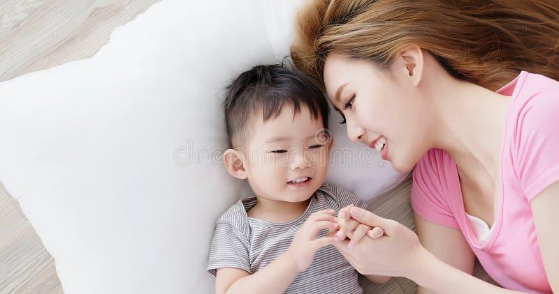 Liggande golv för mamma och för son royaltyfria foton