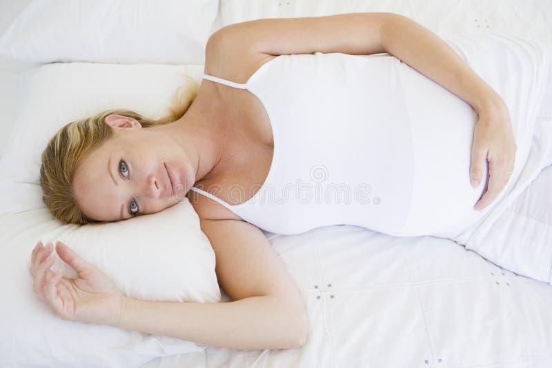 liggande gravid le kvinna för underlag fotografering för bildbyråer