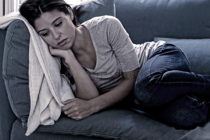 Liggande hemmastadd vardagsrumsoffa för ung attraktiv latinsk kvinna som tröttas och oroas lida fördjupningen som känner sig leds royaltyfria foton