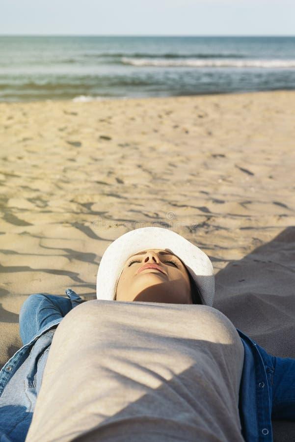 Liggande koppla av för kvinna på stranden royaltyfri bild