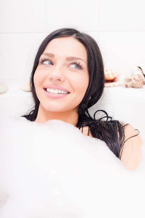 Liggande koppla av för sexig förförisk ung för brunett kvinna för blåa ögon i badet med lyckligt le för skum & se åt sidan closeu royaltyfri bild