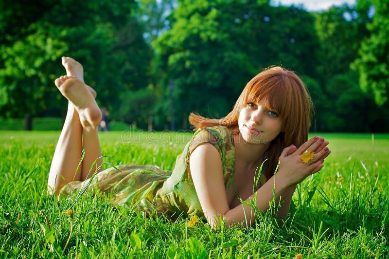 liggande kvinnabarn för härligt gräs royaltyfri foto