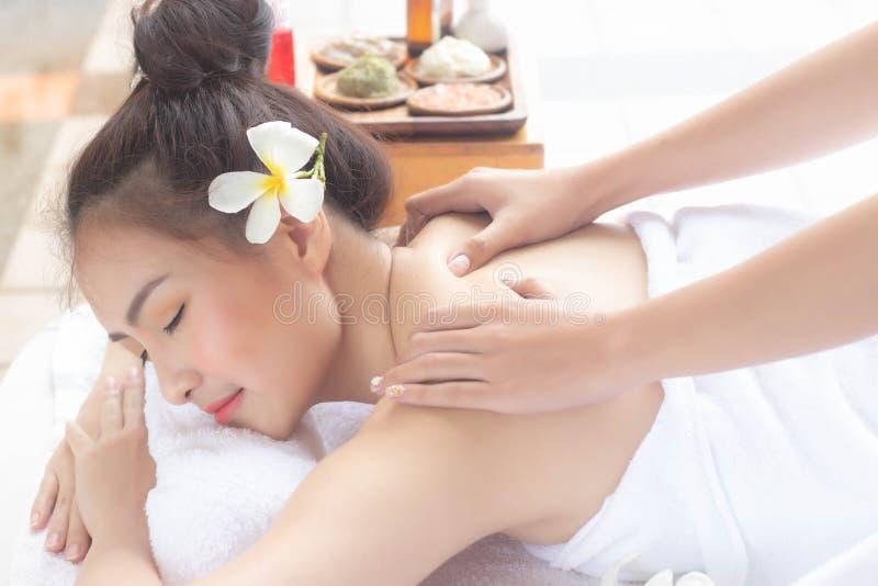 Liggande massagebehandling för härlig asiatisk kvinna med lyckligt lynne på semesterdag Wellnesskroppomsorg och brunnsortaromathe royaltyfri foto
