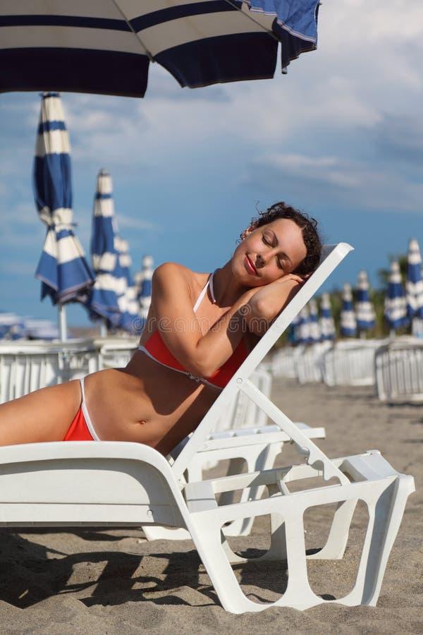 liggande paraply för strandlounger under kvinna arkivbild