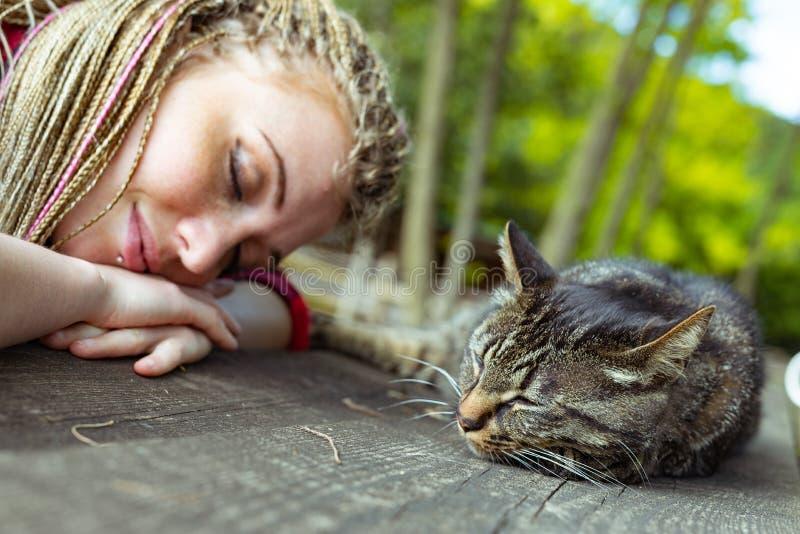 Liggande sova för ung kvinna och för strimmig kattkatt arkivfoto