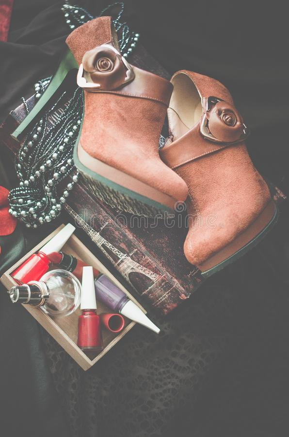 Ligger bruna ankelkängor för mockaskinn på en mörk bakgrund Bredvid asken med kvinnors tillbehör Selektivt fokusera Skjuta fr?n ? royaltyfri bild