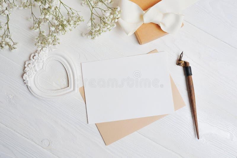 Ligger den övre bokstaven för åtlöje med en förälskelseask i formen av en hjärta på en trävit tabell med gypsophilablommor, ett h royaltyfria bilder