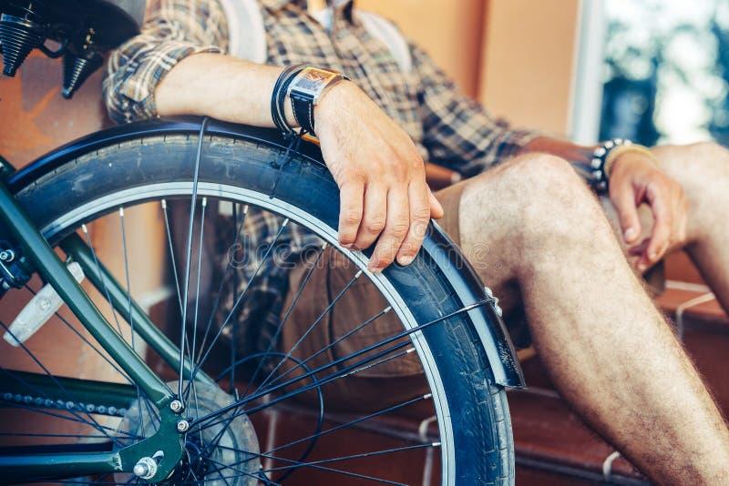 Ligger den unga grabbhanden för closeupen på ett cykelhjul arkivfoton