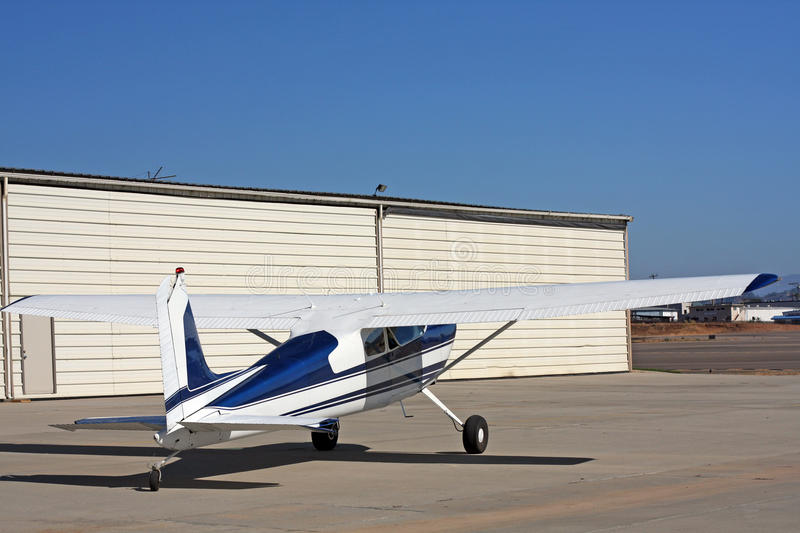 Light aircraft in front of hangar. A light, private airplane (Cessna 180) is in front of a hangar at an airport. Plane is white and blue and was built in 1955 stock photo