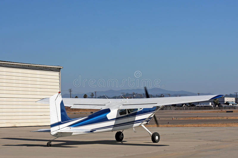 Light aircraft in front of hangar. A light, private airplane (Cessna 180) is in front of a hangar at an airport. Plane is white and blue and was built in 1955 stock image