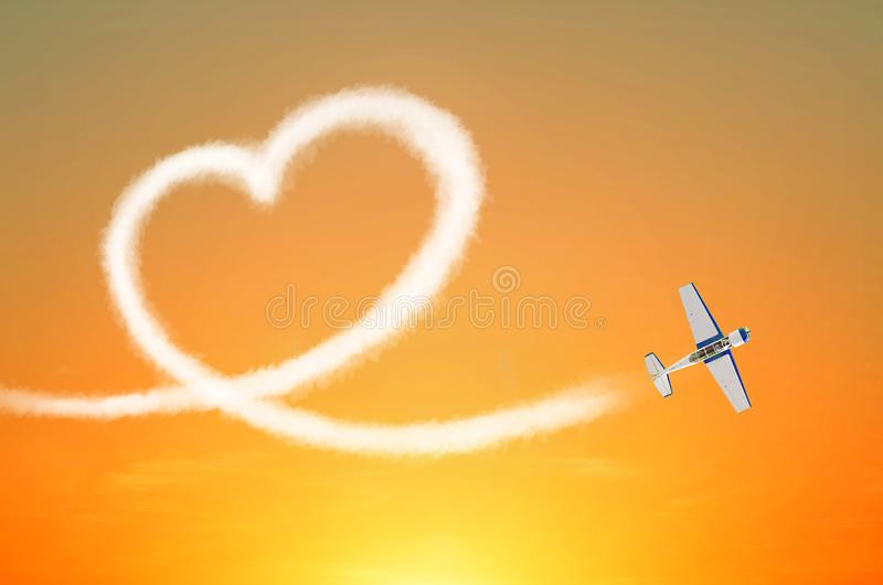 Light aircraft in the sky draws white smoke love heart royalty free stock photography