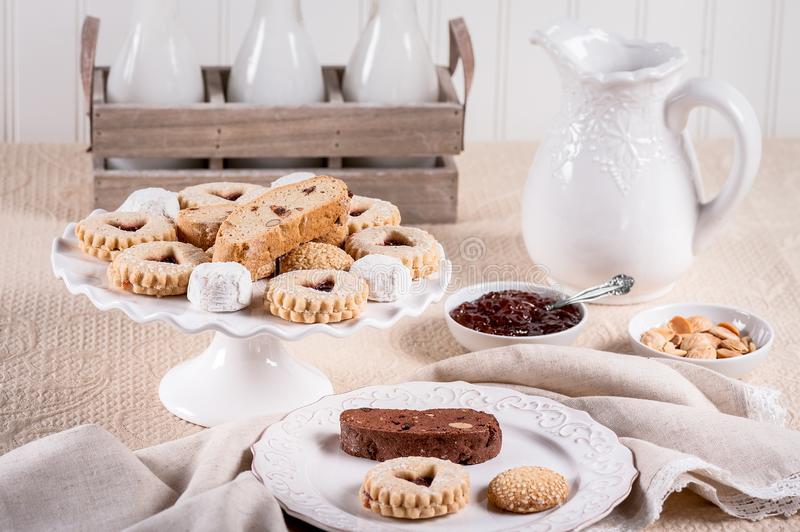 Italian Cookies with jam, almonds, milk bottles and pitcher on a beige colored tablecloth. stock photo