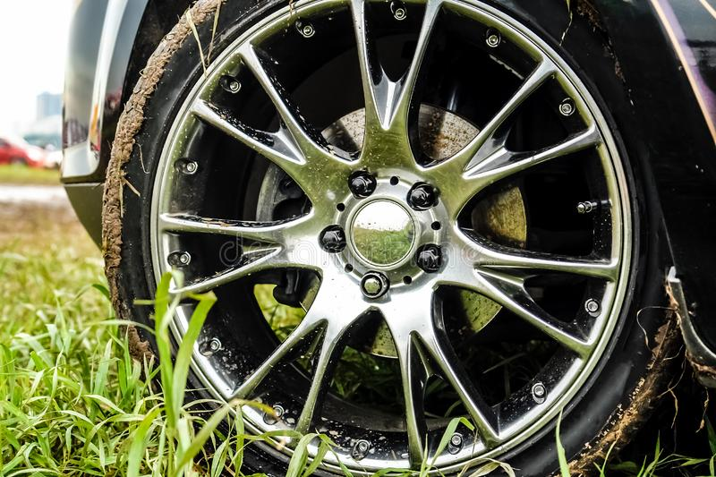 Light alloy wheel of the car is dirty with dirt. The car is on the field.  stock photography